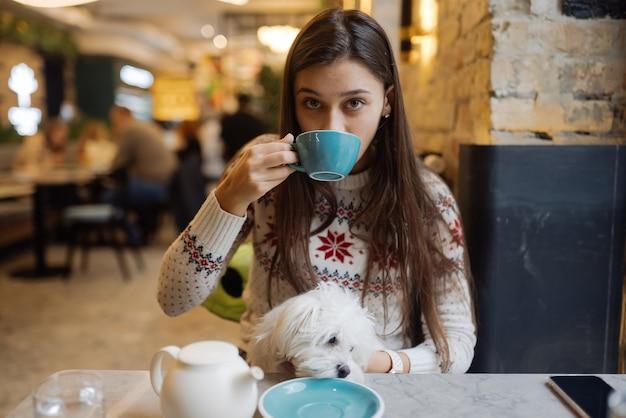 Piękna kobieta trzyma swojego uroczego psa, pije kawę i uśmiecha się w kawiarni