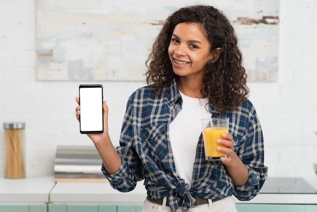 Piękna kobieta trzyma szkło sok i telefon wyśmiewa up