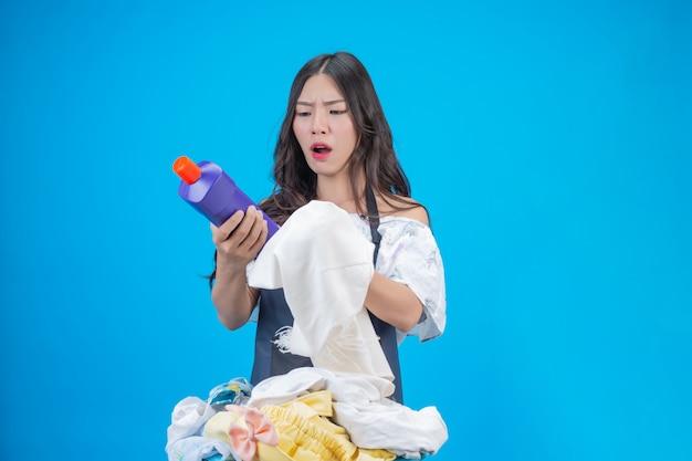 Piękna kobieta trzyma szmatkę i płynny detergent przygotowany do prania na niebiesko