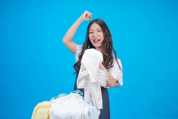 Piękna kobieta trzyma szmatkę przygotowaną do prania na niebiesko