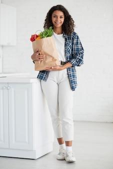 Piękna kobieta trzyma torbę warzywa