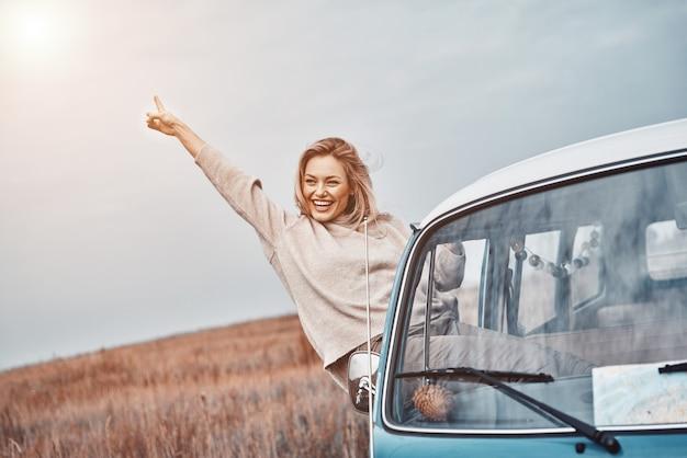 Piękna kobieta trzyma wyciągniętą rękę i wygląda na szczęśliwą, ciesząc się podróżą w mini vanie