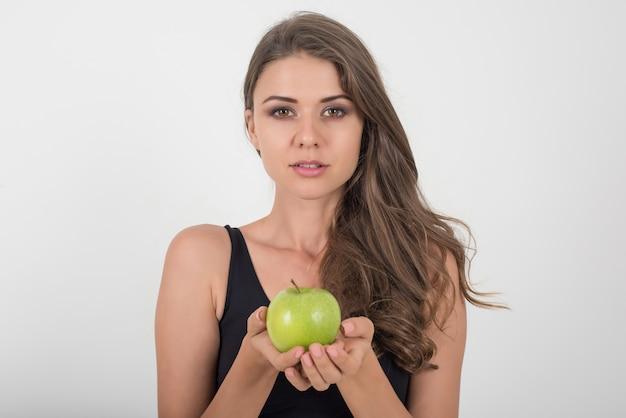 Piękna kobieta trzyma zielone jabłko, podczas gdy na białym tle