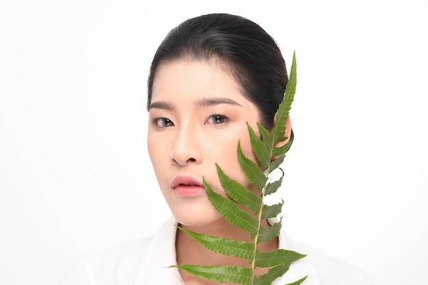 Piękna kobieta trzyma zielonej rośliny.