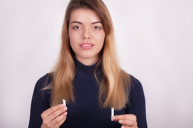 Piękna kobieta trzyma złamanego papierosa. rzucanie papierosów