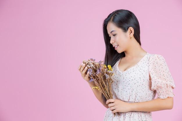 Piękna kobieta trzymać suchy kwiat