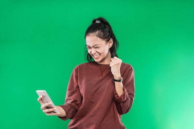 Piękna kobieta trzymając handphone i patrzeć z wyrazem szczęścia, podnosząc jedną rękę i robiąc pięść, odizolowane na zielonym tle