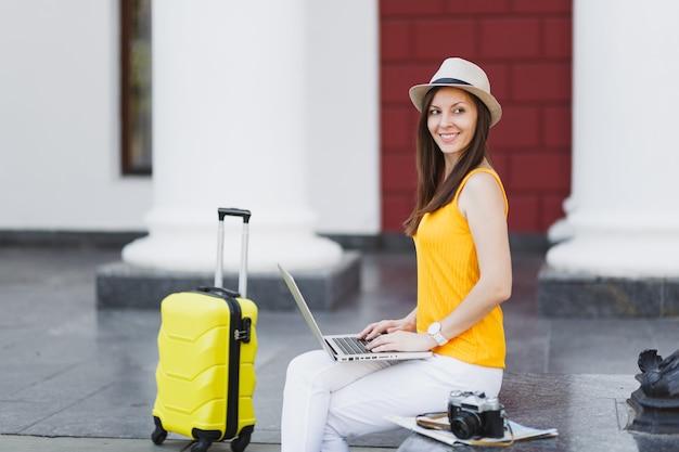 Piękna kobieta turysta podróżnik w kapeluszu z walizką siedzieć za pomocą pracy na komputerze typu laptop pc patrząc na bok w mieście na świeżym powietrzu. dziewczyna wyjeżdża za granicę na weekendowy wypad. styl życia podróży turystycznej.