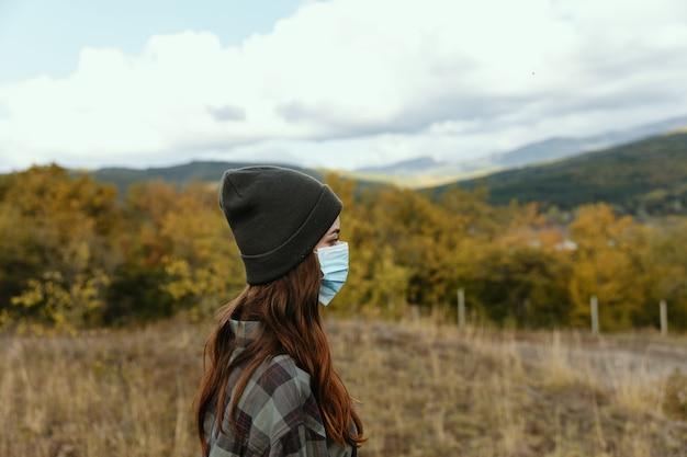 Piękna kobieta turysta w masce medycznej na łące w górach.