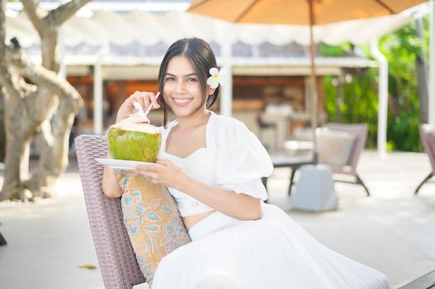 Piękna kobieta turystka z białym kwiatem na włosach pijąca kokos siedząca na leżaku podczas letnich wakacji
