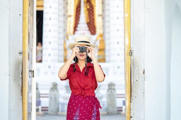 Piękna kobieta turystyczna kamera trzymająca wspomnienia.