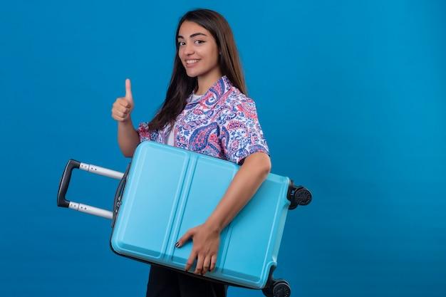 Piękna kobieta turystycznych stojących z walizką podróżną, uśmiechając się wesoło, pokazując kciuki do góry na odizolowanej niebieskiej przestrzeni