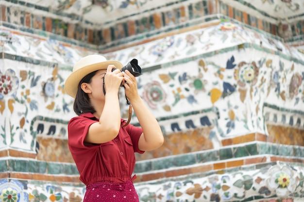 Piękna kobieta turystycznych trzymać aparat, aby uchwycić wspomnienia