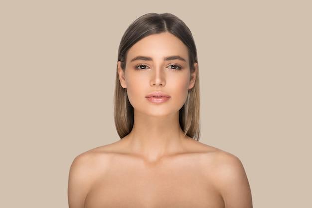 Piękna kobieta twarz portret blondynka. kolor tła. brązowy