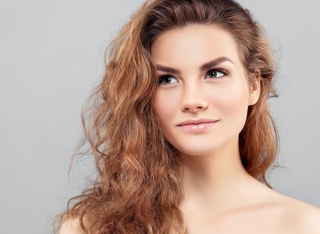 Piękna kobieta twarz studio na szaro z sexy usta i rude włosy. strzał studio.