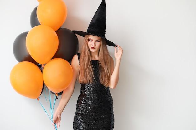 Piękna kobieta ubrana jak czarownica na halloween na świetle