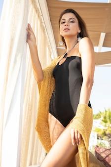Piękna kobieta ubrana w czarny strój kąpielowy