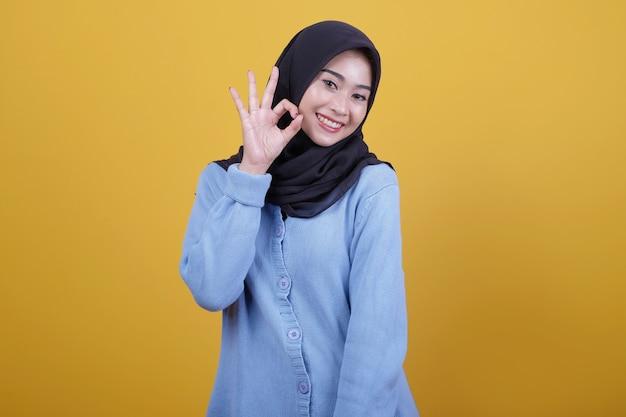 Piękna kobieta ubrana w hidżab z mówiąc okay patrzy szczęśliwie wyrazem