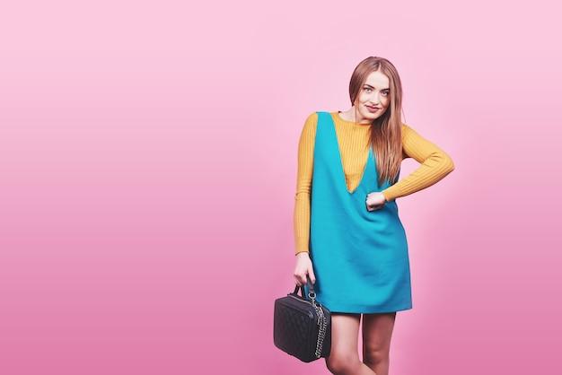 Piękna kobieta, ubrana w ładne ubrania, torebka pozowanie na różowym tle. fotografia mody wiosna.