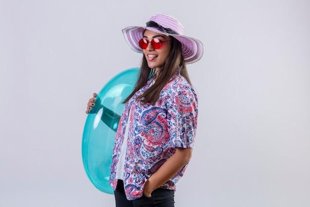 Piękna kobieta ubrana w letni kapelusz i czerwone okulary przeciwsłoneczne, trzymając nadmuchiwany pierścionek, patrząc radośnie wystający język z radosną twarzą stojącą