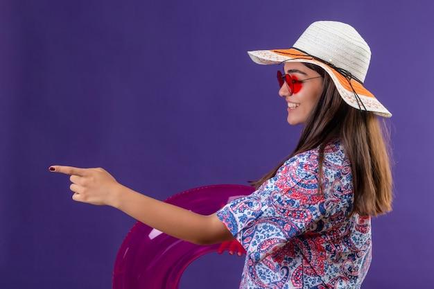 Piękna kobieta ubrana w letni kapelusz i czerwone okulary przeciwsłoneczne, trzymając nadmuchiwany pierścionek stojący bokiem, wskazując palcem w bok, uśmiechając się radośnie