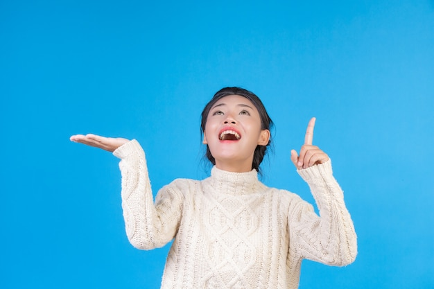 Piękna kobieta, ubrana w nowy biały dywan z długimi rękawami, pokazująca gest na niebiesko. trading.