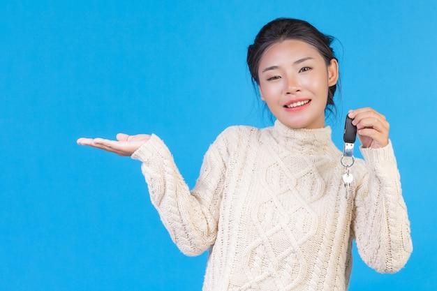 Piękna kobieta ubrana w nowy biały dywan z długimi rękawami, trzymająca w ręku brelok na niebiesko. trading s.