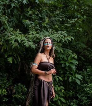 Piękna kobieta ubrana w piórowe piórko ptaków. maluje ciało w kolorze brązowym i twarz w kolorze niebieskim, podnosi ręce w górę, model pozuje w lesie
