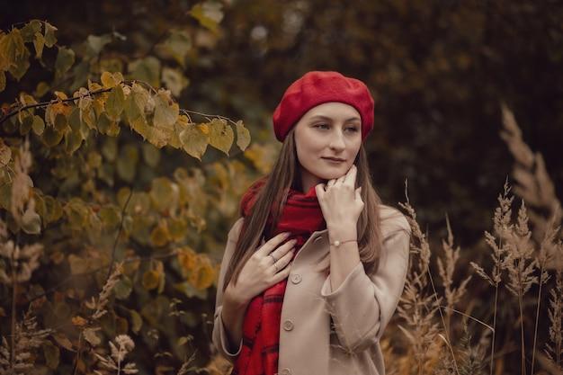 Piękna kobieta ubrana w płaszcz i czerwony beret i szalik w jesienny dzień