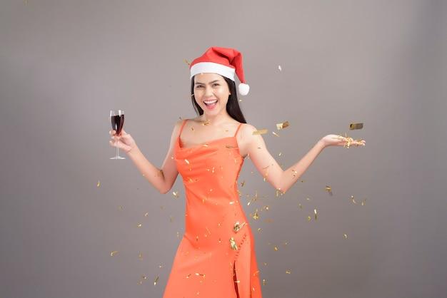Piękna kobieta ubrana w pomarańczową sukienkę z lampką szampana i santa hat