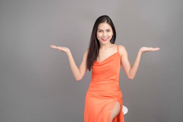 Piękna kobieta ubrana w pomarańczową sukienkę