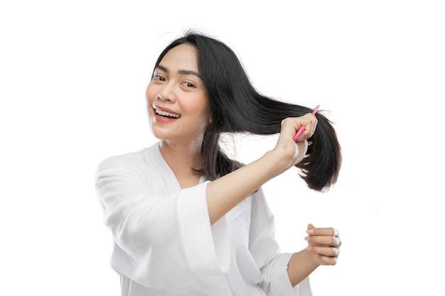 Piękna kobieta ubrana w ręcznik rozczesujący piękne długie włosy grzebieniem