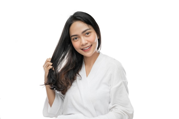 Piękna kobieta ubrana w ręcznik, trzymająca swoje piękne długie włosy palcami na ramieniu
