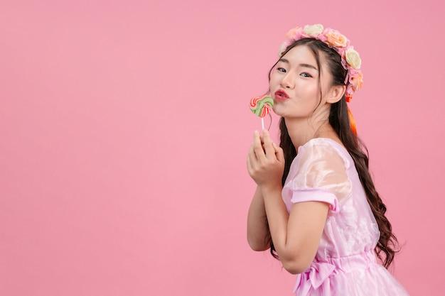 Piękna kobieta ubrana w różową księżniczkę bawi się swoim słodkim cukierek na różu.