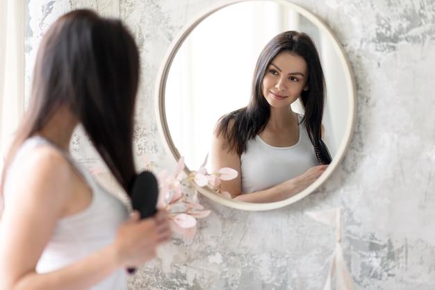 Piękna kobieta układa się w lustrze