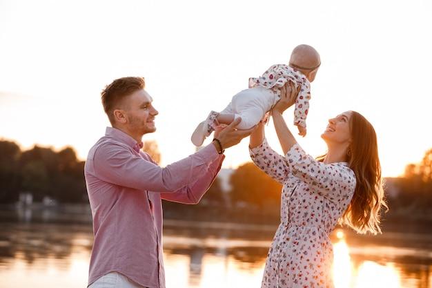 Piękna kobieta unosi wysoko uroczą córeczkę w powietrzu i patrzy na nią z uśmiechem. szczęśliwi rodzice spędza czas bawić się z córką w parku przy zmierzchem. sredni strzał. selektywna ostrość