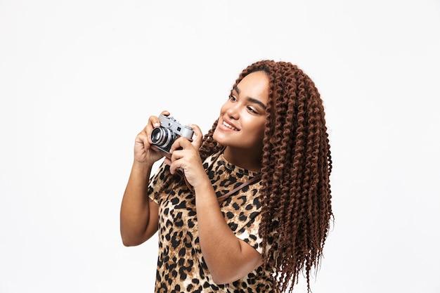 Piękna kobieta uśmiecha się i fotografuje na retro aparacie, stojąc odizolowana od białej ściany