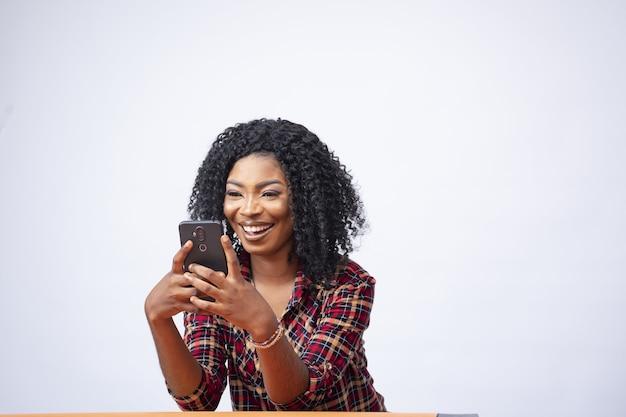Piękna kobieta uśmiecha się i patrzy na swój telefon
