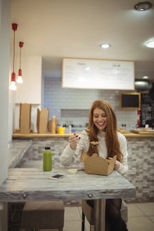 Piękna kobieta uśmiecha się mając sałatkę