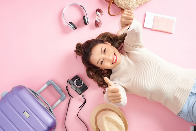 Piękna kobieta uśmiecha się szczęśliwie i pokazuje kciuk do ciebie na różowej podłodze. leżąc z bagażem podróżnym
