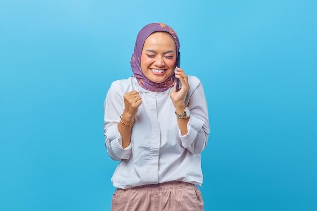 Piękna kobieta uśmiecha się szeroko, dzwoniąc do znajomych przez smartfona