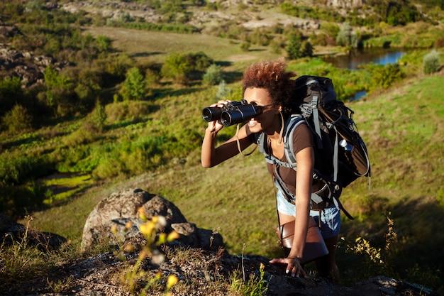 Piękna kobieta uśmiecha się z plecakiem, trzymając lornetki