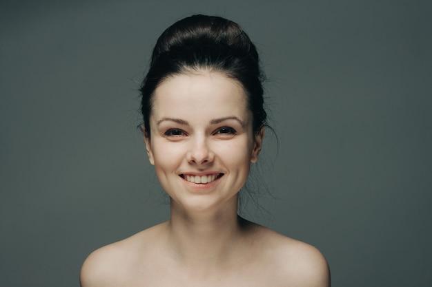 Piękna kobieta uśmiechając się na szare nagie ramiona przycięty widok fryzury.