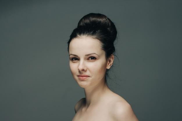 Piękna kobieta uśmiechając się na szare nagie ramiona przycięty widok fryzury