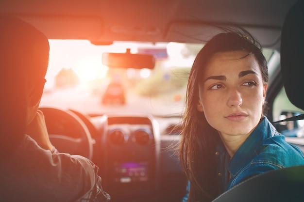 Piękna kobieta uśmiechając się siedząc na przednich siedzeniach pasażera w samochodzie