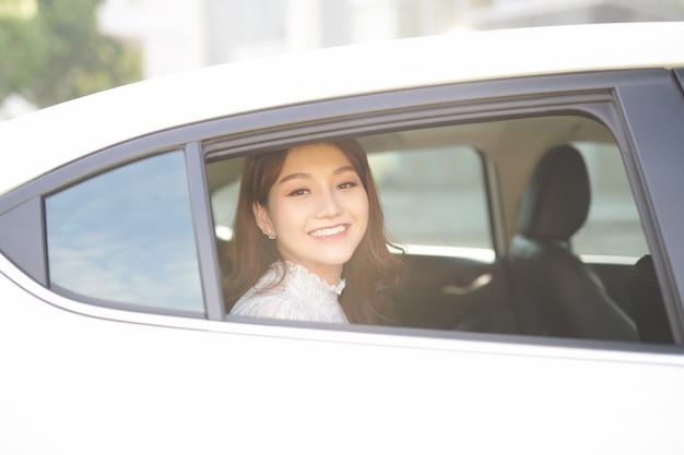 Piękna kobieta uśmiechając się siedząc na tylnym siedzeniu w samochodzie. pani patrzy przez okno.