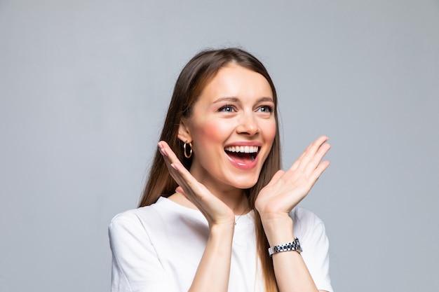 Piękna kobieta uśmiechając się z otwartymi ustami i otwartymi dłońmi na białym tle