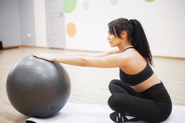 Piękna kobieta uśmiechnięta twarz cieszyć się poćwiczyć z fit ball w fitness