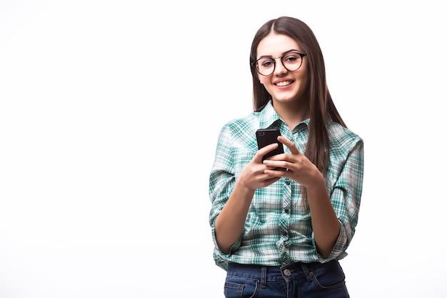 Piękna kobieta używa i czyta inteligentny telefon na białym