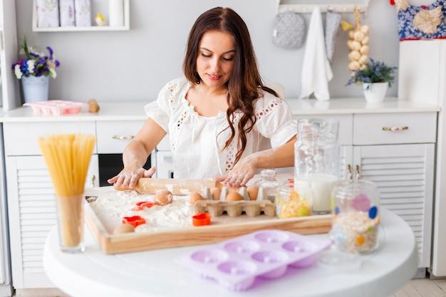 Piękna kobieta używa kuchennego rolownika